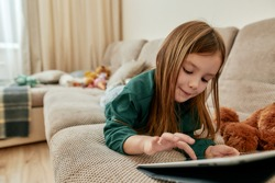 A cute little girl enjoy playing games on her tablet while lying on her stomach on a sofa with her teddybear around in a big bright room being alone at home. Children and modern technologies