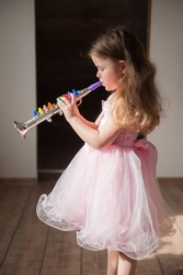 A cute little girl in a lush pink dress plays the toy trumpet.
