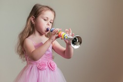 A cute little girl in a lush pink dress plays the toy trumpet. Copy space