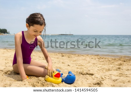 ae74e11fa3 A cute little girl in purple swimming suit playing with toys on the beach  on a