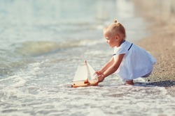 A cute little girl in white clothes playing with a toy ship on the beach on a warm sunny summer day. Holidays at sea. Funny kids