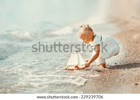 A cute little girl in white clothes playing with a toy ship on the beach on a warm sunny summer day. Holidays at sea. Funny kids #229239706