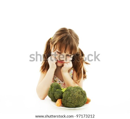 A cute little girl looks in disgust at her plate of vegetables. Isolated on White Background.