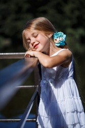 A cute little girl 6 or 7 years old with long blond hair, she is dressed in a ballet summer dress, she is standing on the background of the river