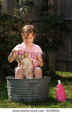 A cute little girl outside washing her Pomeranian puppy in an old, tin tub.