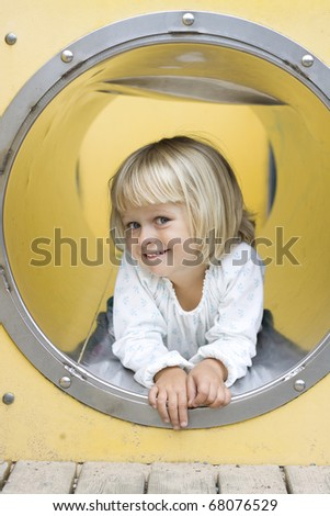 A cute little girl peeking out from a play ground tunnel, smiling at the camera.