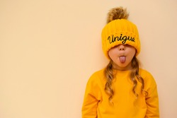 A cute little girl pulls on an orange cap with the words
