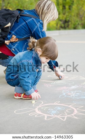 A cute little girl with mom drawing a sketch on a pavement