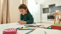 A cute little girl writing with a pencil while sitting at a table having multicolored pencils around the table in a spacy kitchen being alone at home. Creative hobbies concept