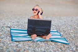A cute little happy girl in pink sunglasses sitting on the striped blue and white mat with a laptop on the beach on a warm summer day. Holiday on a seashore concept. Funny kids. Sea. Ocean.