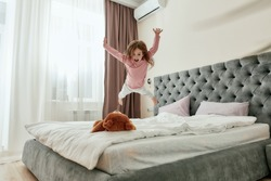A cute little happy girl jumping down like a star on her teddybear barefoot on a bed in a huge bedroom. Happy childhood concept