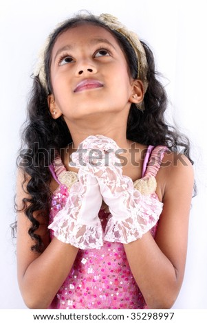 cute little Indian girl praying to god, making a wish, on a white ...