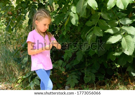 a cute little six year old kid girl walking against a background of green leaves of tree during his summer vacation
