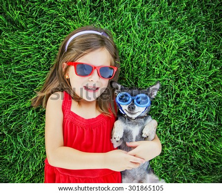 a cute little toddler girl with red sunglasses on holding a tiny chihuahua with blue goggles on laying in the grass in a park or backyard with a nice green lawn