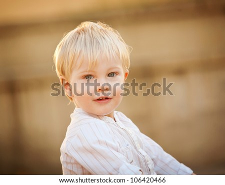 A cute little 1 year old boy against a brick blurred background.  He is smiling and has blonde hair and blue eyes.