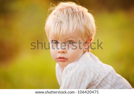 A cute little 1 year old boy sitting indoors on a colorful chair in a kindergarten.  His blue eyes are looking at the camera.