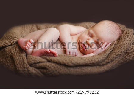 A cute new-born baby sleeping on a knitted brown cushion on black background.