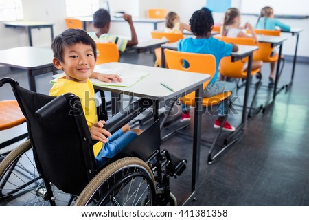 A cute people in wheel chair looking at the camera in classroom