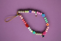 A cute phone charm made with wooden beads and charms.