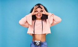 A cute playful girl model, dark-skinned, in a beige crop jacket, a camera hangs around her neck, makes glasses with her hands and smiles.