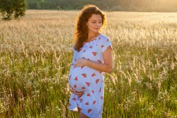 A cute pregnant woman in a beautiful dress is standing in the wheat field at a sunset.Pregnant family photo shoot in nature