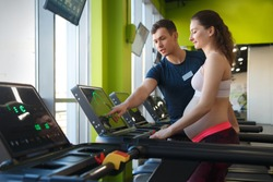 A cute pregnant woman with a big belly is training on a treadmill in the gym under the guidance of a trainer.