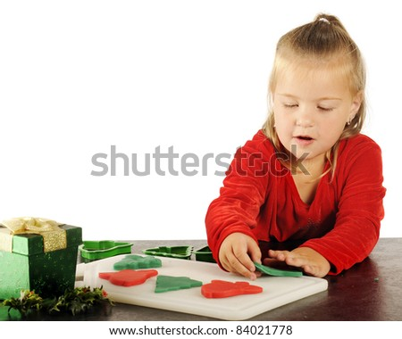 A cute preschooler happily cutting out red and green children's dough cookies for Christmas.  Image has plenty of white space for your test.