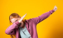 A cute preteen caucasian girl with red hair and freckles is dancing and doing the dab dance move. Happy little white red-haired is dabbing and laughing to the sound of trap music. Milennials and Gen Z