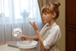 A cute redhead girl 10 years old in an apron prepares meringues in the home kitchen. The girl licks her finger, savoring the whipped egg whites.