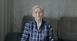 A cute Senior woman looks at the camera. A granny with gray hair and deep wrinkles is resting.