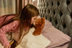 A cute small girl kissing a teddybear in his nose wishing goodnight before sleeping while lying in a big bed next to it in a well-lightened bedroom. Childhood concept