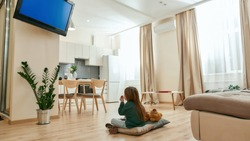 A cute small girl sitting on the floor cross-legged watching TV eating cereal balls in the middle of a spacy bright room being alone at home. Childrens leisure activities