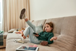 A cute small girl wondering what to watch on a TV holding a TV remote sitting on a sofa in a big room with a bowl of cereal balls being alone at home. Childrens leisure activities