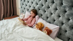 A cute small happy girl lying with teddybears in a huge bed covered with blanket smiling and reading book aloud. relaxing in a big bright bedroom at home