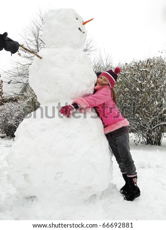 A cute small happy  girl posing with her big snowman.