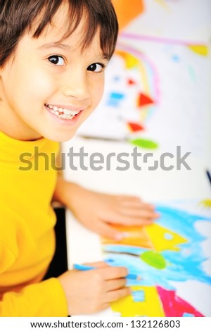 A cute smiling little boy is drawing and being creative