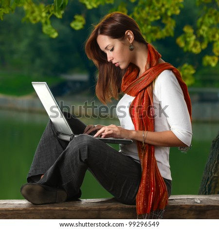a cute student girl in red neckerchief working with laptop outdoor summer time close to pond