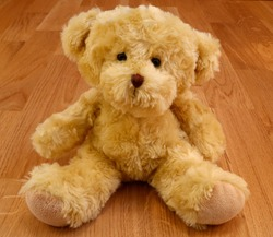 A cute stuffed teddy bear. Softly smiling kindly. Close up and isolated against a wooden background.