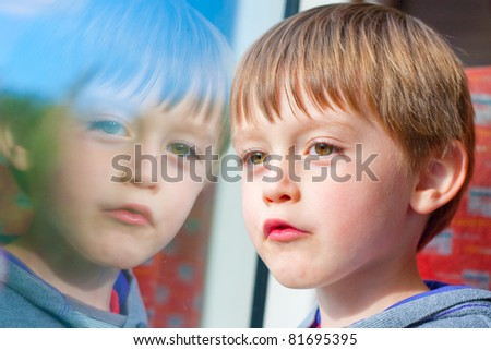 A cute three year old looks out of a train window on a summer day