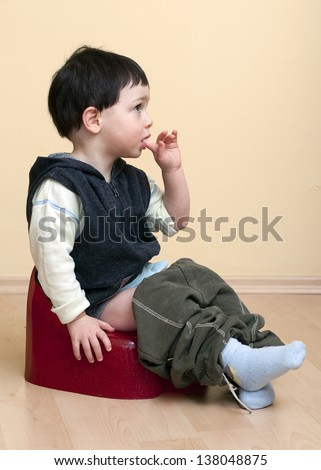 A cute toddler child boy sitting on a red potty.
