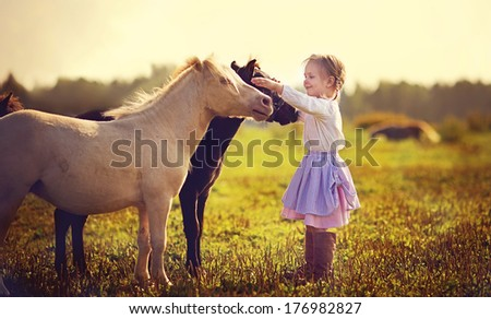 A cute white girl in jockey boots caressing her little pony in the field on a sunny summer day