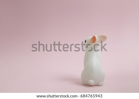 a cute white plastic bunny on a pink background.