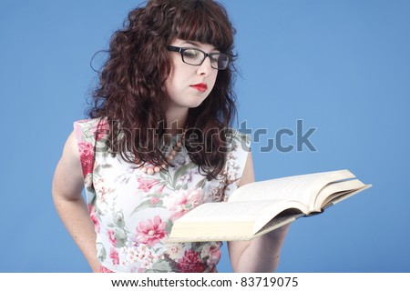 A cute woman wearing glasses reading a book.