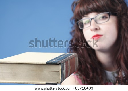 A cute woman wearing glasses with a book.