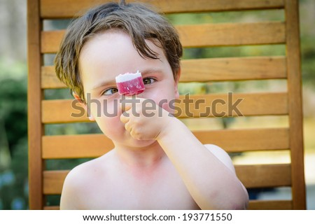 A cute 4 year old boy looking at a lolly cross eyed on a hot summers day