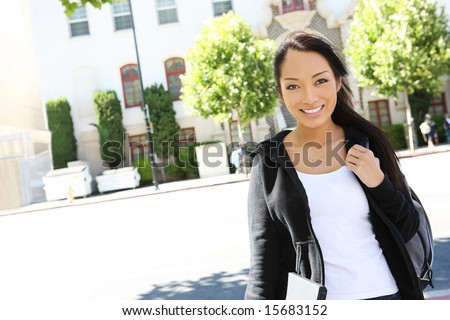 A cute young asian woman walking to class on college campus