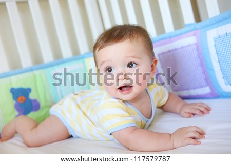 A cute young baby boy in a crib smiling