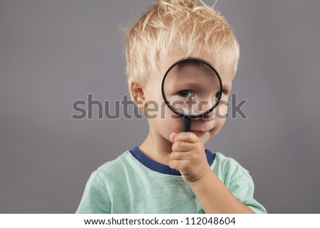 A cute young boy holds a magnifying glass up to his eye. - stock photo