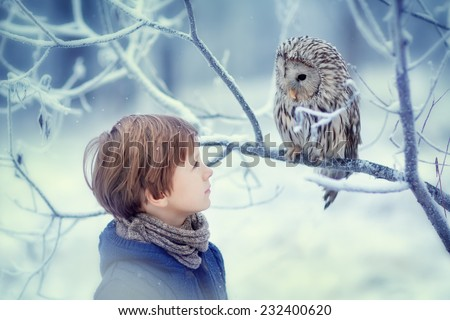 A cute young boy in a warm knitted clothes looking at the owl sitting on the branch covered with frost on a frosty winter day. Kids and nature.