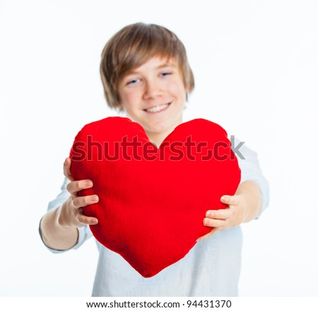 A cute young boy in love with a red plush heart in his hands. Focus on the heart.